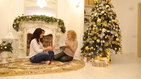 Beautiful sisters prepare each other surprises and chatting, sitting on floor in bright living room with festive. Blonde woman gives sister and girlfriend New stock video
