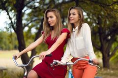 Beautiful sisters riding bicycles in park. Outdoor portrait Royalty Free Stock Image
