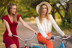 Beautiful sisters riding bicycles in park. In summer Royalty Free Stock Photos