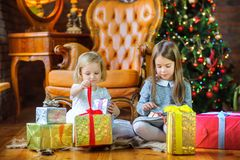 Beautiful sisters sit on the floor near the Christmas tree stock photos