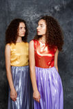 Beautiful sisters twins in bright dresses posing over grey background. Royalty Free Stock Images