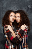 Beautiful sisters twins posing looking at camera over grey background. Royalty Free Stock Image