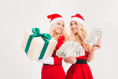Beautiful sisters twins in red santa claus clothes and hats Royalty Free Stock Photography