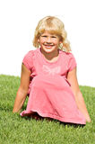Beautiful six year old girl. A beautiful, cherubic six year old blond girl sits in a grassy field stock photography