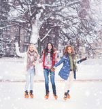 Young and pretty girl skating on outdoor open air ice-rink at wi Royalty Free Stock Photos