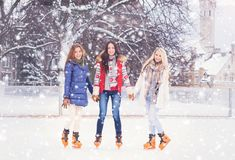 Young and pretty girl skating on outdoor open air ice-rink at wi Royalty Free Stock Image