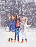 Young and pretty girl skating on outdoor open air ice-rink at wi royalty free stock photography