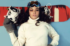 Beautiful skier girl with dark hair wears ski equipment. Fashion studio photo of beautiful skier girl with dark hair wears ski equipment stock photography