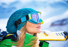 Beautiful skier girl portrait. Closeup portrait of beautiful skier girl wearing mask and holding ski, enjoying winter holidays royalty free stock image