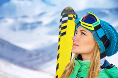 Beautiful skier girl portrait. Closeup portrait of beautiful skier girl wearing mask and holding ski, enjoying winter holidays in Europe royalty free stock photo