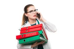 Attractive caucasian brunette confident female doctor standing in office with binders in her hands talking on phone on stock image