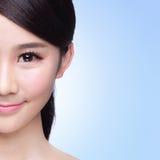 Beautiful Skin care woman Face. Half of Beautiful Skin care woman Face smile to you  on blue background. asian Beauty Stock Photography