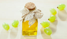 Beautiful skincare and haircare composition. Bottle of natural grapeseed oil and green fresh grapes on wooden table Royalty Free Stock Photography