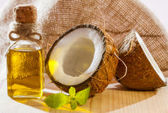 Beautiful skincare and haircare concept. Fresh coconut, bottle of oil and mint leaf on wooden table - beautiful skincare and haircare composition Royalty Free Stock Photo