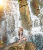 Beautiful skinny girl posing on the background of a waterfall splashing water and bright sun. Royalty Free Stock Images