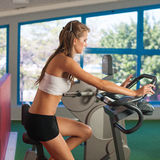 Beautiful skinny woman riding a bike in fitness Stock Photography