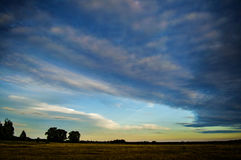 Beautiful sky with clouds at sunset. Sky with clouds at sunset over the meadow Stock Photos