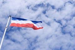 National Dutch Flag with blue cloudy sky Stock Photo