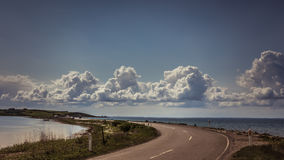 Beautiful sky and perfect road going through Danish countryside. Royalty Free Stock Images