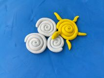 Beautiful sky, sun and cloud dough, blue background. Beautiful sky made from plasticine clay on blue background, cute sun and cloud shaped dough stock photo