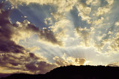 Beautiful sky with sunbeams and dynamic clouds at sunset. Royalty Free Stock Image