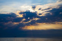 Beautiful sky at sunrise over the sea. Seascape. Sun`s rays shine through the clouds stock image