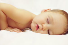 Beautiful sleeping baby on white. Close-up portrait of a beautiful sleeping baby on white Stock Image