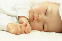 Beautiful sleeping baby on white. Close-up portrait of a beautiful sleeping baby on white Royalty Free Stock Photography