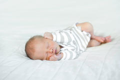 A beautiful sleeping newborn baby boy on a white blanket.  He is. The newborn is lying on his side with his hands near his face.   The small baby is sleeping Stock Photo
