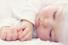 Beautiful sleeping newborn baby on white. Close-up portrait of a beautiful sleeping newborn baby on white stock photography