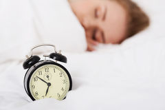 Beautiful sleeping woman with alarm clock. Royalty Free Stock Images