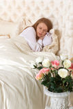 Beautiful sleeping woman in bed with roses. Romance. Beautiful sleeping woman in white bed with red roses Royalty Free Stock Photos