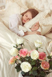 Beautiful sleeping woman in bed with roses. Romance. Beautiful sleeping woman in white bed with red roses Royalty Free Stock Images