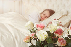 Beautiful sleeping woman in bed with roses Stock Photos