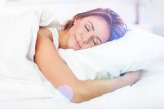 Free Beautiful Sleeping Woman In White Bed With Flares Royalty Free Stock Photos - 110822908