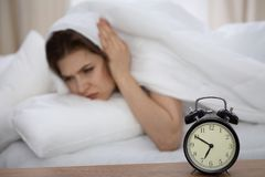 Beautiful sleeping woman lying in bed and trying to wake up with alarm clock. Girl having trouble with getting up early Royalty Free Stock Photography