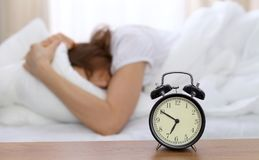 Beautiful sleeping woman lying in bed and trying to wake up with alarm clock. Girl having trouble with getting up early Stock Image