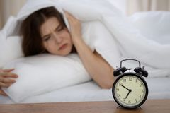 Beautiful sleeping woman lying in bed and trying to wake up with alarm clock. Girl having trouble with getting up early. In the morning, Nightmare Royalty Free Stock Photos