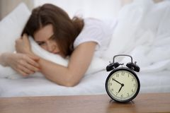 Beautiful sleeping woman lying in bed and trying to wake up with alarm clock. Girl having trouble with getting up early. In the morning, Nightmare Stock Photo