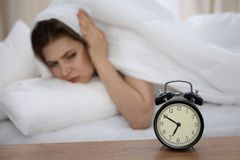 Beautiful sleeping woman lying in bed and trying to wake up with alarm clock. Girl having trouble with getting up early. In the morning, Nightmare Stock Photos