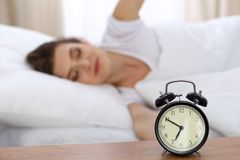 Beautiful sleeping woman resting in bed and trying to wake up with alarm clock.  Stock Photos