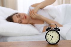 Beautiful sleeping woman resting in bed and trying to wake up with alarm clock.  Royalty Free Stock Image