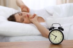Beautiful sleeping woman resting in bed and trying to wake up with alarm clock.  Royalty Free Stock Photography