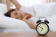 Beautiful sleeping woman resting in bed and trying to wake up with alarm clock.  Stock Photography