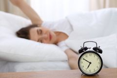 Beautiful sleeping woman resting in bed and trying to wake up with alarm clock.  Royalty Free Stock Images
