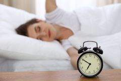 Beautiful sleeping woman resting in bed and trying to wake up with alarm clock.  Stock Photo