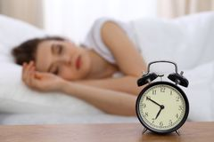 Beautiful sleeping woman resting in bed and trying to wake up with alarm clock.  Royalty Free Stock Photos
