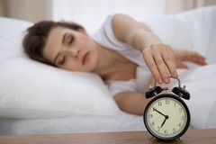 Beautiful sleeping woman resting in bed and trying to wake up with alarm clock.  Royalty Free Stock Photo