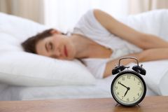 Beautiful sleeping woman resting in bed and trying to wake up with alarm clock.  Stock Image