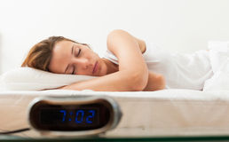 Beautiful sleeping young woman in bad with alarm clock Royalty Free Stock Photos